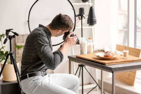 Young man taking picture of food in photo studio Фото со стока