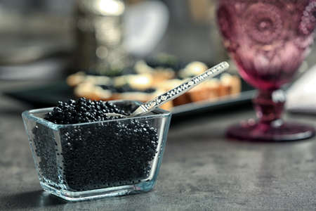 Glass bowl with black caviar on table