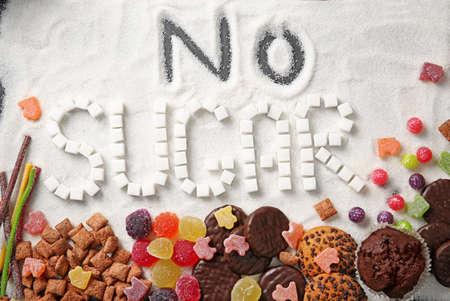 Composition with phrase NO SUGAR and sweets on sugar sand Archivio Fotografico
