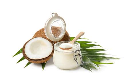 Tarro con aceite de coco y nueces sobre fondo blanco. Foto de archivo