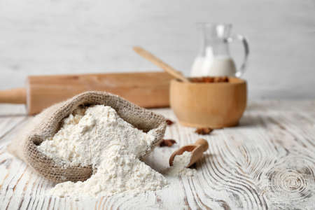 Sack with flour on wooden table