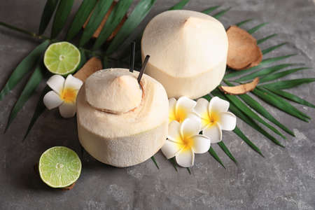 Composition with fresh coconut drink in nut on grey background Stock Photo