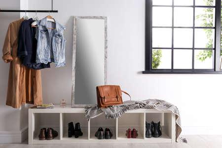 Nowoczesne wnętrze przedpokoju z wiszącymi ubraniami i półką na buty