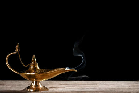 Aladdin magic lamp on table against black background