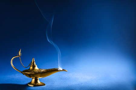 Aladdin magic lamp on blue background Standard-Bild - 104088965