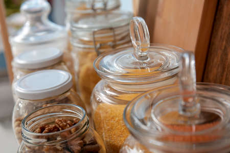 Glass jars with different foodstuff on shelf indoors