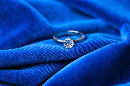 Beautiful engagement ring on blue fabric, closeup