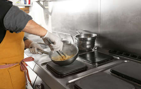 Male chef cooking pasta in restaurant kitchen Stock Photo