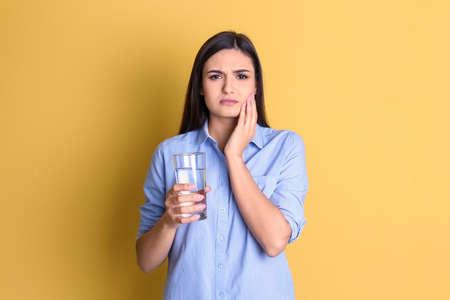 Jonge vrouw met gevoelige tanden en glas koud water op kleurenachtergrond Stockfoto