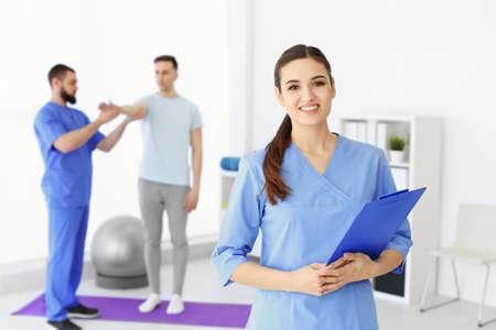 Joven fisioterapeuta con portapapeles en centro de rehabilitación