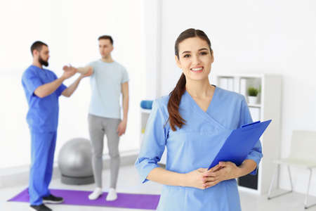 Young physiotherapist with clipboard in rehabilitation center Stock Photo