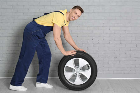 Male mechanic with car tire on brick wall background