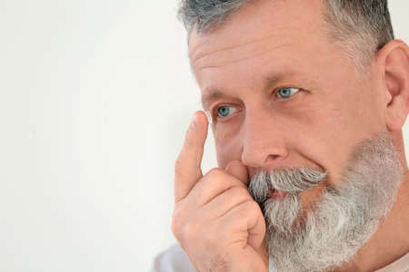 Senior man putting contact lens in his eye on light background Stock Photo