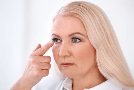 Senior woman putting contact lens in her eye on light background