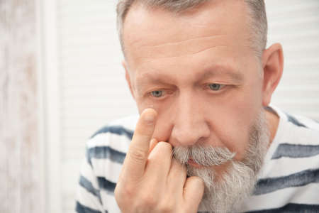 Senior man putting contact lens in his eye indoors