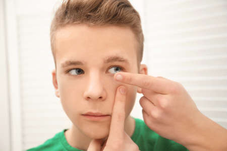 Teenage boy putting contact lens in his eye indoors Archivio Fotografico