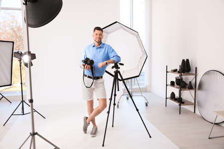 Professional photographer with camera and lighting equipment in studio Stock Photo