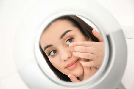 Mirror reflection of young woman putting contact lens in her eye
