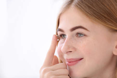 Teenage girl putting contact lens in her eye on white background