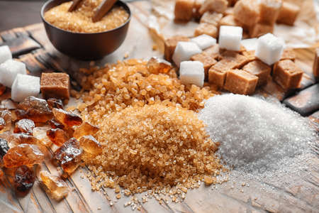Different types of sugar on wooden table