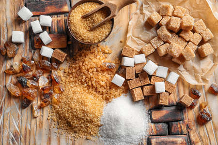 Flat lay composition with different types of sugar on wooden table Фото со стока