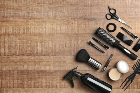 Flat lay composition with professional hairdresser tools on wooden background Stock Photo