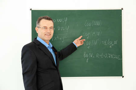 Portrait of male teacher near blackboard in classroom