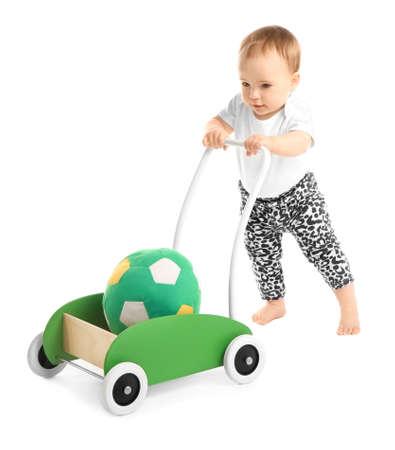 Lindo bebé con andador de juguete sobre fondo blanco. Foto de archivo