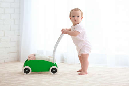 Cute baby with toy walker indoors