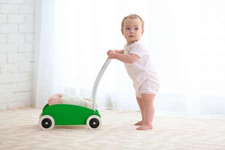 Nettes Baby mit Spielzeugwanderer drinnen