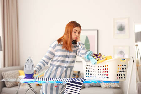 Tired housewife ironing clothes at home Stock Photo