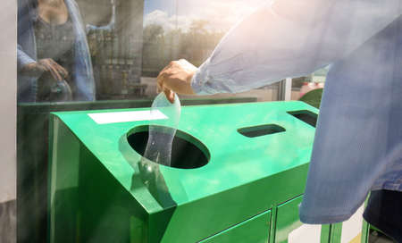 Woman throwing plastic bottle into litter bin outdoors. Recycling concept
