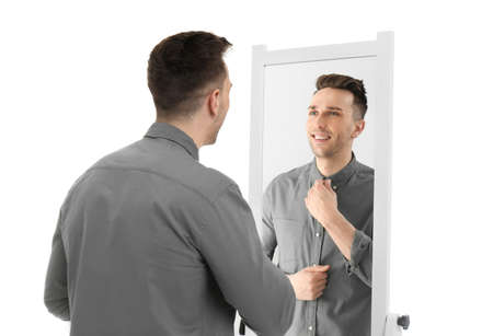Young man looking at himself in mirror on white background Foto de archivo