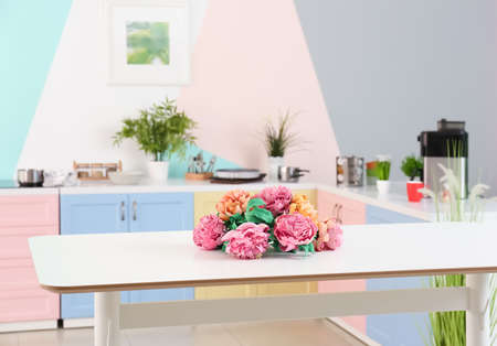 Flowers on table in colorful kitchen Stock Photo