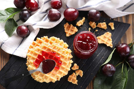 Composition with delicious homemade plum jam and waffles on dark wooden board Banco de Imagens