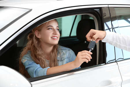 Young woman receiving key while sitting on driver's seat of car