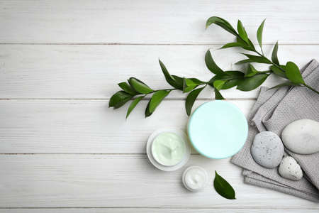Composition with body cream in jars on wooden background, top view