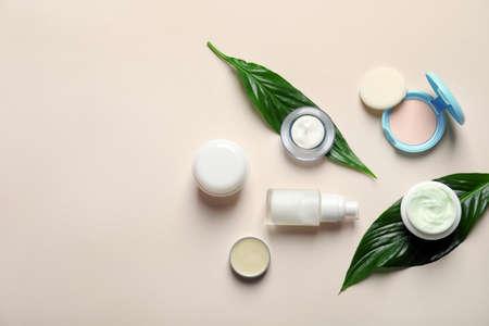 Différents produits cosmétiques de soins de la peau avec des feuilles vertes sur fond clair, vue du dessus Banque d'images
