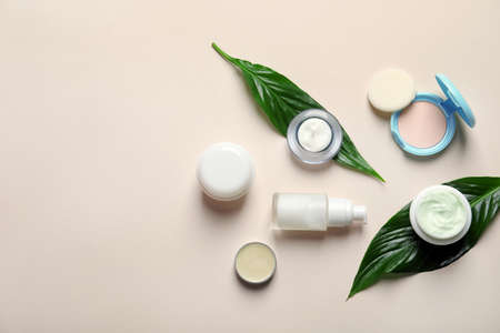 Different skin care cosmetic products with green leaves on light background, top view