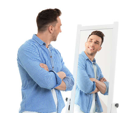 Young man looking at himself in mirror on white background