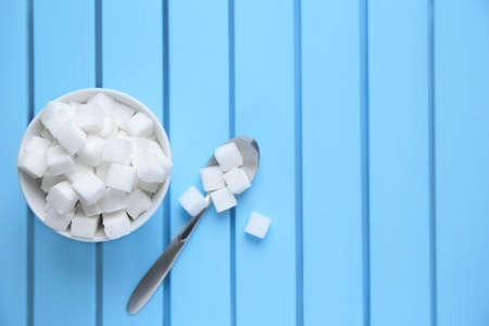 Bowl with refined sugar cubes on color wooden background, top view Imagens