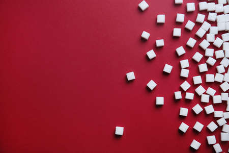 Refined sugar cubes on color background, top view