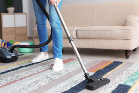 Man hoovering carpet with vacuum cleaner at home Stock Photo