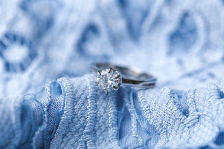Beautiful engagement ring on blue lace, closeup