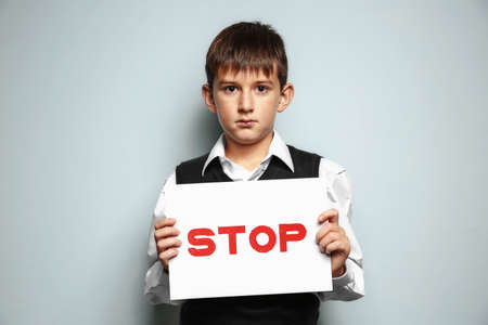Little boy holding sign with word Stop on light background