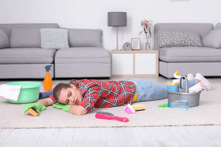 Tired woman sleeping on floor after cleaning carpet at home