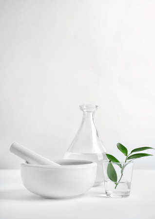 Composition with mortar and pestle on table against light background. Homemade cosmetic products Stock Photo