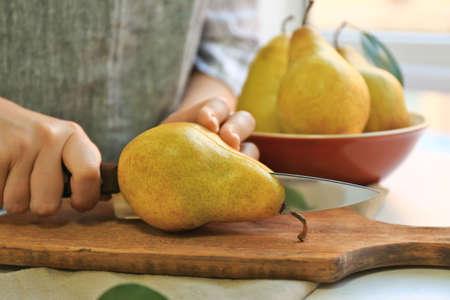 Young woman cutting fresh ripe pear on wooden board Archivio Fotografico
