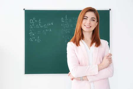 Beautiful young teacher near blackboard in classroom