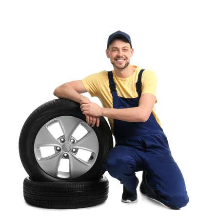 Male mechanic with car tires on white background Reklamní fotografie